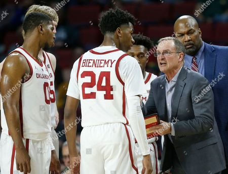 Oklahoma head coach Lon Kruger, right, talks with his players in the first half of an NCAA college basketball game against Baylor in Norman, Okla