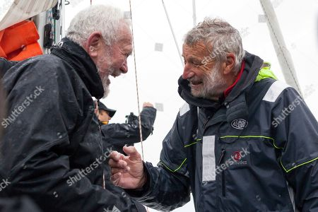 French sailor Jean-Luc Van Den Heede, 73, right, aboard his Rustler 36, Matmut, is congratulated by legendary sailor Sir Robin Knox-Johnston of Britain, after winning the Golden Globe Race, a single-handed round the world yacht race, after 212 days alone at sea, in Les Sables-d'Olonne harbor, western France