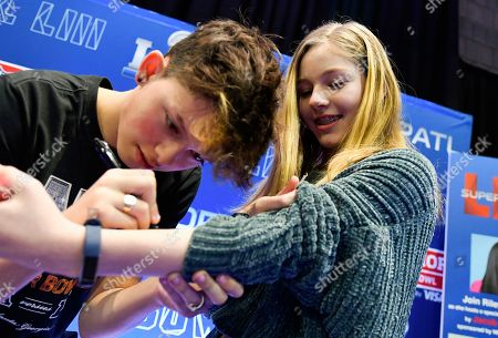 Jacob Sartorius signs and autograph for a fan at the NFL Shop on in Atlanta