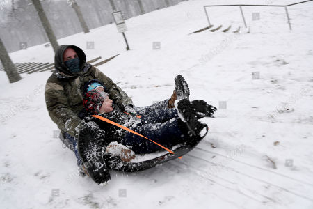 Mike Riker, left, rides a sled with his sons, Julian, 4, front, and Eli, 2, at Hopatcong State Park during the early part of a snowstorm, in Landing. The snowstorm is expected to last through the evening commute hours in the northwestern region of New Jersey and freezing is predicted for Wednesday
