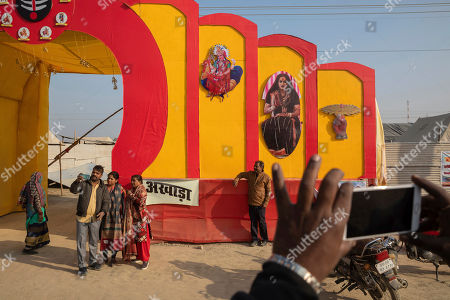 "Hindu devotees take snapshots by the entrance to ""Kinnar akhara,"" a monastic order formed by Laxmi Narayan Tripathi, who is among India's best-known transgender activists, during the Kumbh Mela festival in Prayagraj, India. The Kinnars' tent camp on the edge of the festival grounds is adorned with Ardhanari, the androgynous composite image of the Hindu god Shiva and his consort Parvati, that religious scholars date to the 1st century. Tripathi is trying to break into the male-dominated world of Hinduism's high priests gathered this month in the north Indian city of Prayagraj on the Ganges river for the weeks-long Kumbh Mela festival, where tens of millions of Hindus travel every three years to take a holy dip"