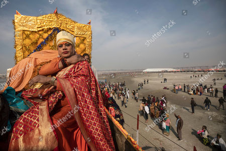 "A member of the ""Kinnar Akhara"" monastic order sits on a carriage during a procession on auspicious Makar Sankranti day during the Kumbh Mela festival in Prayagraj, Uttar Pradesh state, India. Unlike other akharas, which are only open to Hindu men, Kinnar, founded in 2015, is open to all genders and religions. On the Kumbh's first bathing day, transgender activist Laxmi Narayan Tripathi led a train of 21 tractor chariots from their tent camp to the bathing ghats with devotees following on foot as observers showered them with flower petals"
