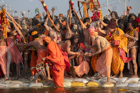 "Hindu holy men from one of the ancient and most orthodox akharas ""Juna akhara"" take a dip on auspicious Makar Sankranti day during the Kumbh Mela festival in Prayagraj, Uttar Pradesh state, India. The Juna Akhara is the only monastic order to have accepted the newly formed Kinnar Akhara, led by transgender activist Laxmi Narayan Tripathi. Unlike other akharas, which are only open to Hindu men, Kinnar, founded in 2015, is open to all genders and religions"