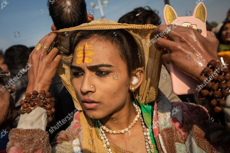 "An Indian hijra walks on the banks after taking a dip along with other members of the newly formed ""Kinnar akhara"" monastic order on the auspicious Makar Sankranti day during the Kumbh Mela festival in Prayagraj, Uttar Pradesh state, India. Unlike other akharas, which are only open to Hindu men, Kinnar, founded in 2015, is open to all genders and religions. This is the first time the newly formed Kinnar Akhara, or monastic order, has set up camp at the massive temporary city in Prayagraj, led by transgender activist Laxmi Narayan Tripathi"
