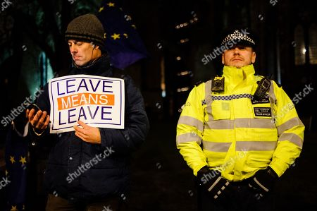 A man holds a pro-Brexit placard beside a police officer as activists demonstrate outside the Houses of Parliament in central London. In the Commons, on a day of significant parliamentary activity over Brexit, MPs voted down a cross-party amendment tabled by Labour Party MP Yvette Cooper and Conservative Party MP Nick Boles designed to substantially reduce the risk of a much-feared 'no-deal' exit from the EU. An amendment rejecting the principle of a no-deal exit was meanwhile approved, as was a government-backed amendment championed by Conservative Party MP Graham Brady calling for 'alternative arrangements' to take the place of the controversial Irish 'backstop' provision in the withdrawal agreement negotiated with the EU.