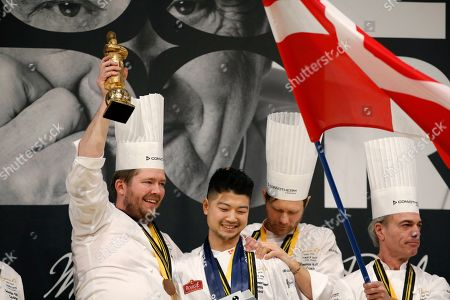 First place winner Danish chef Kenneth Toft-Hansen (L) and his commis Christian Wellendorf Kleinert (2-L) hold their trophy next to team coach Rasmus Kofoed (2-R) and team president Francis Cardenau (R) as they celebrate on the podium after competing in the final event of the Bocuse d'Or International culinary competition at the Sirha International Hotel Catering and Food trade Exhibition, in Lyon, France, 30 January 2019.