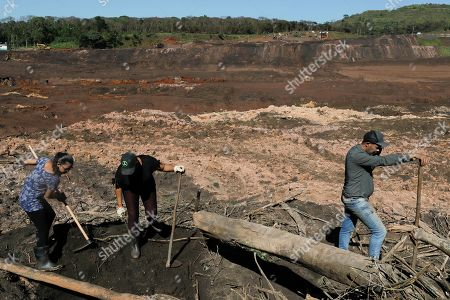 """Stock Picture of Tereza Ferreira Nascimento, center, her sister-in-law Sonia Santos, left, and her brother Pedro Ferreira dos Santos dig with garden tools in search of the body of Tereza's and Pedro's missing brother Paulo Giovane Santos, days after a mining company's dam collapsed in Brumadinho, Brazil, . """"We are here since Friday taking turns between brothers, brothers-in-law, searching for the body so that we can at least give him a dignified burial,"""" said Nascimento, holding back tears. """"So far it has been in vain"""