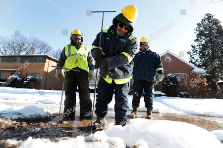 Richard James, a Detroit Water and Sewerage worker, uses a poking rod to find a water main break in Detroit