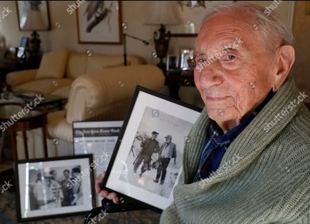 """Novelist, playright and editor A.E. Hotchner, who was Ernest Hemingway's close friend and biographer, holds photographs of him and Hemingway from the 1950's in Ketchum, Idaho, where they went duck hunting together, at his home in Westport, Conn. When the 1958 film adaptation """"The Old Man and the Sea"""" hit theaters, Hemingway told his close friend that he hated it and urged his writer pal to do his own adaptation someday. Hotchner, now 101, has finally completed his friend's request, and the stage adaptation of """"The Old Man and the Sea,"""" done in collaboration with son Tim, is set to premiere in Pittsburgh on Feb. 1. Hotchner also co-founded Newman's Own with Paul Newman"""