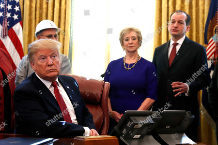 """President Donald Trump listens as Labor Secretary Alex Acosta, right, speaks during a meeting with American manufacturers in the Oval Office of the White House, in Washington. Trump was signing an executive order pushing those who receive federal funds to """"buy American."""" Small Business Administrator Linda McMahon is second from right"""
