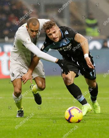 Inter Milan's Joao Miranda, left, challenges for the ball with Lazio's Ciro Immobile during an Italian Cup quarterfinal soccer match between Inter Milan and Lazio at the San Siro stadium, in Milan, Italy
