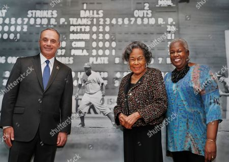 """Rob Manfred, Rachel Robinson, Sharon Robinson. Major League Baseball Commissioner Rob Manfred, left, Rachel Robinson, center, widow of the late Jackie Robinson, and Sharon Robinson, the couple's daughter, pose in front of a mural-sized photograph of Jackie Robinson in uniform displayed at the Museum of the City of New York, in New York. The photo is part of """"In the Dugout with Jackie Robinson,"""" an exhibition celebrating Robinson's 100th birthday, mounted in collaboration with The Jackie Robinson Foundation. The exhibit features 30 photographs originally shot for Look Magazine (most never published) and rare Robinson family home movies plus memorabilia related to Robinson's career"""