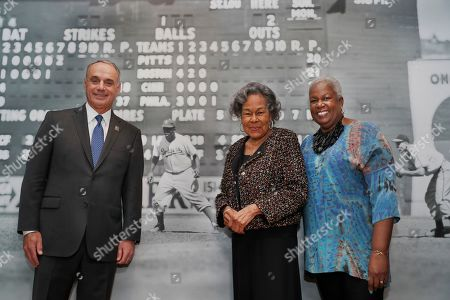 """Major League Baseball Commissioner Rob Manfred, left, Rachel Robinson, widow of the late Jackie Robinson, and Sharon Robinson, the couple's daughter, pose in front of a mural-sized photograph of Jackie Robinson playing the outfield displayed at the Museum of the City of New York, in New York as part of an exhibition celebrating Robinson's 100th birthday. """"In the Dugout with Jackie Robinson: An Intimate Portrait of a Baseball legend,"""" mounted in collaboration with The Jackie Robinson Foundation, features 30 photographs originally shot for Look Magazine (most that were never published), rare home movies of the Robinson family plus memorabilia related to Robinson's career"""