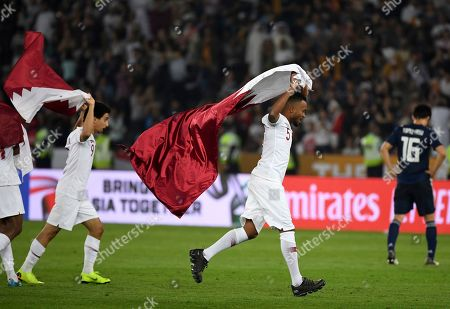 Qatar's midfielder Ahmed Fathi, center, and Qatar's midfielder Khaled Mohammed, left, run to celebrate past Japan's defender Takehiro Tomiyasu, right, after winning the AFC Asian Cup final match between Japan and Qatar in Zayed Sport City in Abu Dhabi, United Arab Emirates