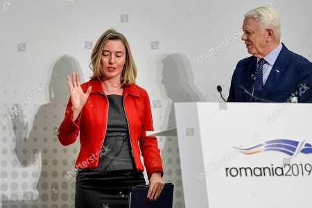 European Union Foreign Policy chief Federica Mogherini, left, gestures at the end of a joint press conference with Romania's Foreign Minister Teodor Melescanu, right, during a Gymnich meeting of EU foreign ministers in Bucharest, Romania