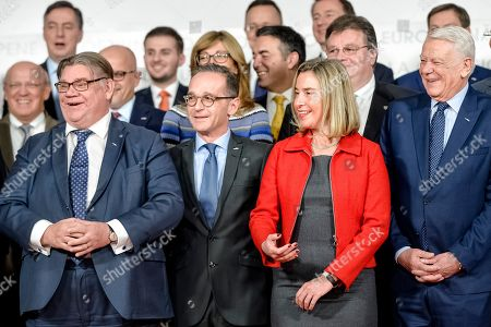 Finland's Foreign Minister Timo Soini, front left, alongside Germany's Foreign Minister Heiko Maas, European Union's Foreign Policy chief Federica Mogherini, center right, and Romania's Foreign Minister Teodor Melescanu, right, react to the late arrival of an EU member during a Gymnich meeting of EU foreign ministers in Bucharest, Romania
