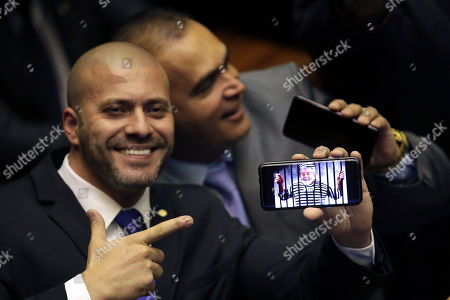 Deputy Daniel Silveira, who was elected to his first term representing the Social Liberal Party from where President Jair Bolsonaro mounted his campaign, points to his phone showing an image spoofing the jailed President former President Luiz Inacio Lula da Silva, during a swearing-in ceremony in the Chamber of Deputies, in Brasilia, Brazil