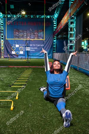 World renowned gymnast and gold medalist Gabby Douglas stretches before running through a clinic with Hall of Fame Running Back LaDainian Tomlinson, hosted by the NFL Extra Points Credit Card issued by Barclays,, in Atlanta at Super Bowl Experience in the Georgia World Congress Center