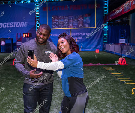 World renowned gymnast and gold medalist Gabby Douglas snaps a selfie with Hall of Fame Running Back LaDainian Tomlinson before running through a VIP clinic hosted by the NFL Extra Points Credit Card issued by Barclays,, in Atlanta at Super Bowl Experience in the Georgia World Congress Center