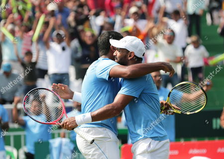 India's Rohan Bopanna (L) and Divij Sharan (R) celebrate after winning their doubles match against Matteo Berrettini and Simone Bolelli of Italy at the Davis Cup qualifiers round tie between India and Italy in Kolkata, eastern India, 02 February 2019.