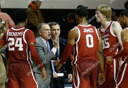 Oklahoma head coach Lon Kruger talks with his team during a timeout in the second half of an NCAA college basketball game against Oklahoma State in Stillwater, Okla