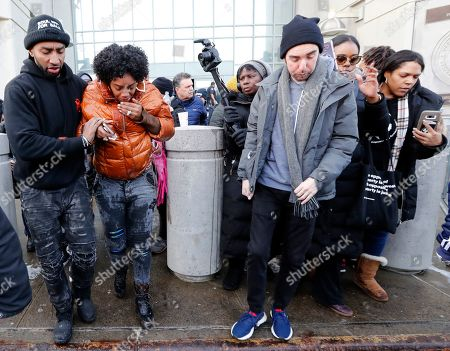 Yandy Smith, second from left, is helped by others after she joined protesters and prisoners' family members in storming the main entrance of the Metropolitan Detention Center, in the Brooklyn borough of New York, in protest of conditions at the facility. The federal prison has been without heat, hot water, electricity and sanitation since mid-week, including throughout the recent frigid weather