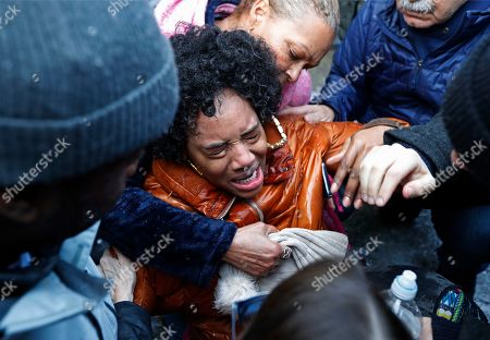 Protesters help Yandy Smith after she received pepper spray following she and others stormed the main entrance to the Metropolitan Detention Center, a federal facility where prisoners have gone without heat, hot water and flushing toilets due to an electrical outage, in New York