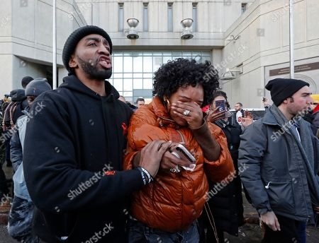 A man helps Yandy Smith after she received pepper spray when she and others stormed the main entrance to the Metropolitan Detention Center, a federal facility where protesters say prisoners have gone without heat, hot water and flushing toilets due to an electrical outage, in New York