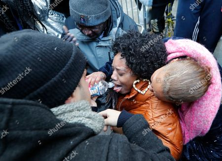 Protesters help Yandy Smith who was sprayed with pepper spray after she and others, including inmates family members, stormed the main entrance to the Metropolitan Detention Center, in New York. Prisoners have been without heat, hot water, electricity and sanitation due to an electrical failure since earlier in the week, including during the recent frigid cold snap