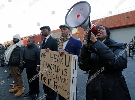 U.S. Rep. Yvette Clarke, D-New York, far right, stands beside Brooklyn Borough President Eric Adams, uses a megaphone to amplify her voice so prisoners can hear her, as the pair joined family members, protesters, and activists holding a vigil outside the Metropolitan Detention Center, in New York. Prisoners have been without heat, hot water, electricity and sanitation due to an electrical failure since earlier in the week, including during the recent frigid cold snap