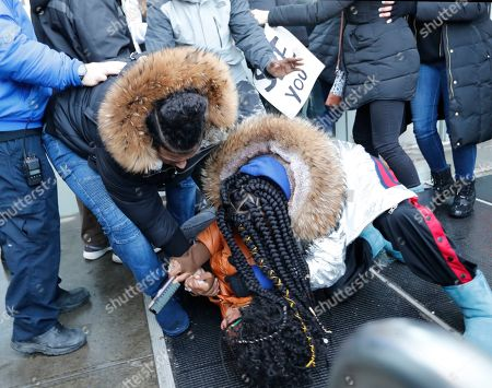 Yandy Smith lies on the ground as people come to her rescue after she was sprayed with a respiratory irritant and thrown to the ground after she and other protesters, prisoners' family members stormed the main entrance to the Metropolitan Detention Center, in the Brooklyn borough of New York