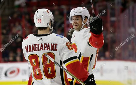 Calgary Flames' Andrew Mangiapane (88) and Derek Ryan celebrate Ryan's goal against the Carolina Hurricanes during the second period of an NHL hockey game in Raleigh, N.C