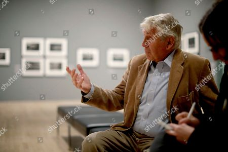 Veteran British conflict photographer Don McCullin speaks during an interview with The Associated Press at the launch of his retrospective exhibition at the Tate Britain gallery in London, . The exhibition includes over 250 of his black and white photographs, including conflict images from the Vietnam war, Northern Ireland, Cyprus, Lebanon and Biafra, alongside landscape and still life images
