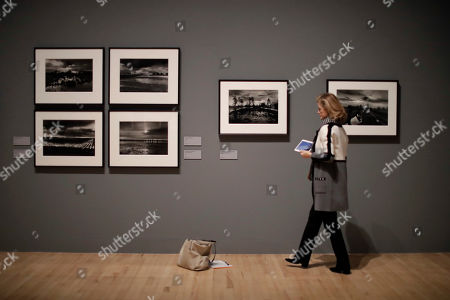 A visitor looks at landscape photographs by veteran British conflict photographer Don McCullin at the launch of his retrospective exhibition at the Tate Britain gallery in London, . The exhibition includes over 250 of his black and white photographs, including conflict images from the Vietnam war, Northern Ireland, Cyprus, Lebanon and Biafra, alongside landscape and still life images