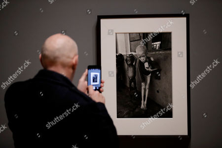 A visitor takes a photo of a 1968 photograph of a starving albino boy in Biafra by veteran British conflict photographer Don McCullin at the launch of his retrospective exhibition at the Tate Britain gallery in London, . The exhibition includes over 250 of his black and white photographs, including conflict images from the Vietnam war, Northern Ireland, Cyprus, Lebanon and Biafra, alongside landscape and still life images