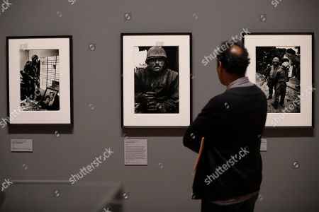 British conflict photographer Don McCullin's photograph, center, of a shell-shocked U.S. marine from the Battle of Hue from the Vietnam War in 1968 is displayed at the launch of his retrospective exhibition at the Tate Britain gallery in London, . The exhibition includes over 250 of his black and white photographs, including conflict images from the Vietnam war, Northern Ireland, Cyprus, Lebanon and Biafra, alongside landscape and still life images