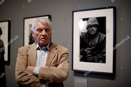 Veteran British conflict photographer Don McCullin poses for photographers next to his 1968 photograph of a shell-shocked U.S. marine from the Battle of Hue in the Vietnam War at the launch of his retrospective exhibition at the Tate Britain gallery in London, . The exhibition includes over 250 of his black and white photographs, including conflict images from the Vietnam war, Northern Ireland, Cyprus, Lebanon and Biafra, alongside landscape and still life images