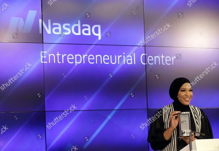 Olympic fencer Ibtihaj Muhammad smiles before pushing a button to ring the Nasdaq Stock Market closing bell at the Nasdaq Entrepreneurial Center in San Francisco, . Muhammad, the first Muslim-American woman to compete for the U.S. wearing a hijab, won a bronze medalist at the 2016 Summer Olympics in Rio de Janeiro, Brazil