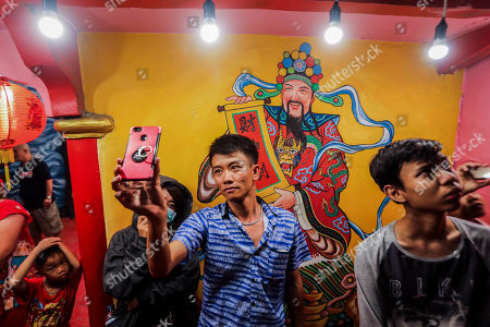 Stock Picture of An Indonesian man take pictures on his mobile phone as he watches fireworks  during the Chinese New Year eve celebrations at the Pak Pie Hut Cou temple in Medan, North Sumatra, Indonesia, 05 February 2018. Chinese around the world celebrate the Chinese New Year, also called Spring Festival, which this year falls on 05 February.