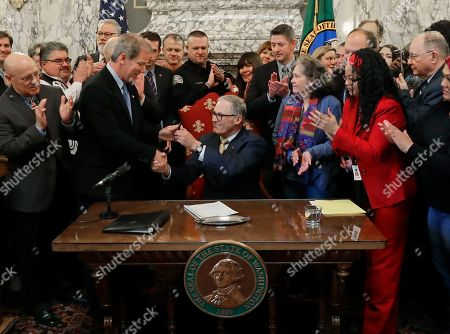 Stock Picture of Washington Gov. Jay Inslee, center, hands a pen to Rep. Roger Goodman, D-Kirkland, chairman of the House Public Safety Committee, after Inslee signed a bill sponsored by Goodman that revised Initiative 940, the measure voters passed in November 2018 to make it easier to prosecute police officers for negligent shootings, at the Capitol in Olympia, Wash. The bill alters language about when officers can be held liable for using deadly force