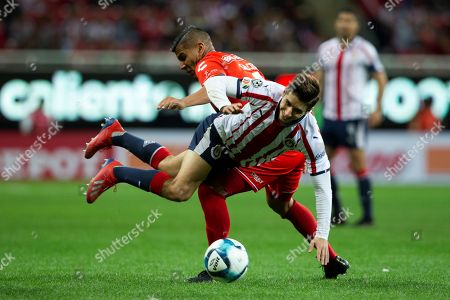 Chivas' Isaac Brizuela (front) vies for the ball with Veracruz's Carlos Salcido (back) during the Mexican tournament soccer match between Chivas and Veracruz at Akron stadium in Guadalajara, Mexico, 04 February 2019.