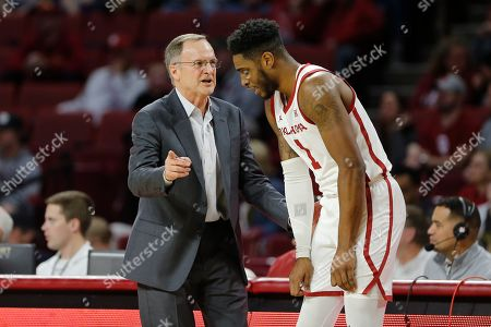 Oklahoma head coach Lon Kruger, left, coaches Oklahoma guard Rashard Odomes, right, during a break in play in the first half of an NCAA college basketball game in Norman, Okla