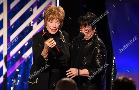 Shirley MacLaine, Kathy Bates. Shirley MacLaine, left, accepts the Career Achievement award from Kathy Bates during the 18th Annual Movies For Grownups Awards at Beverly Wilshire Hotel, in Beverly Hills, Calif