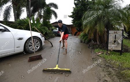 Corbin Dale cleans the driveway of a friend's house in the suburb of Hermit Park in Townsville, Queensland, Australia, 05 February 2019. Residents have begun cleaning up after days of torrential rain and unprecedented water releases from the city's swollen dam, sending torrents of water down the Ross River and into the city, swamping roads, yards and homes.