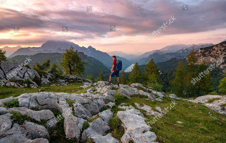 MODEL RELEASED Hiker at the summit of Feldkogel, mountain landscape, view of Koenigssee at sunset, left Watzmann Suedspitze and Watzmannkinder, Berchtesgaden National Park, Berchtesgadener Land, Upper Bavaria, Bavaria, Germany