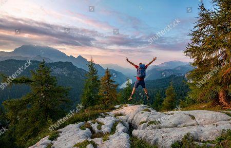 MODEL RELEASED Hiker jumps, summit of Feldkogel, view of Koenigssee at sunset, left Watzmann Suedspitze and Watzmannkinder, Berchtesgaden National Park, Berchtesgadener Land, Upper Bavaria, Bavaria, Germany