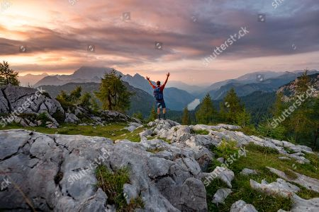 MODEL RELEASED Hiker stretches his arms into the air, summit of Feldkogel, view of Koenigssee at sunset, left Watzmann Suedspitze and Watzmannkinder, Berchtesgaden National Park, Berchtesgadener Land, Upper Bavaria, Bavaria, Germany