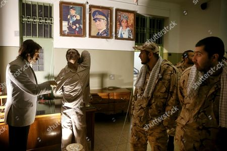 Iranian Revolutionary Guard soldiers look at an exhibition at a former prison run by the pre-revolution intelligence service, SAVAK, now a museum, where wax mannequins of an interrogator and a prisoner being tortured, are on display, in Tehran, Iran. Portraits of the shah, Queen Farah and his son, Crown Prince Reza Pahlavi, who now lives in exile in the U.S., hang above the scene