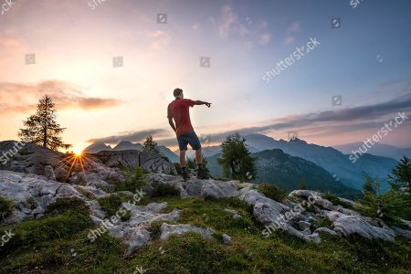 MODEL RELEASED Hiker shows in the distance, last sunrays at the summit of the Feldkogel at sunset, mountain landscape, national park Berchtesgaden, Berchtesgadener Land, Upper Bavaria, Bavaria, Germany