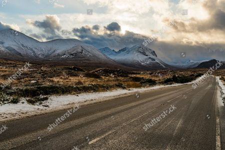 Snowy mountain tops of Ben Lee with clouds in Highland landscape and road cup in the foreground, Sligachan, Portree, Isle of Sky, Scotland, United Kingdom